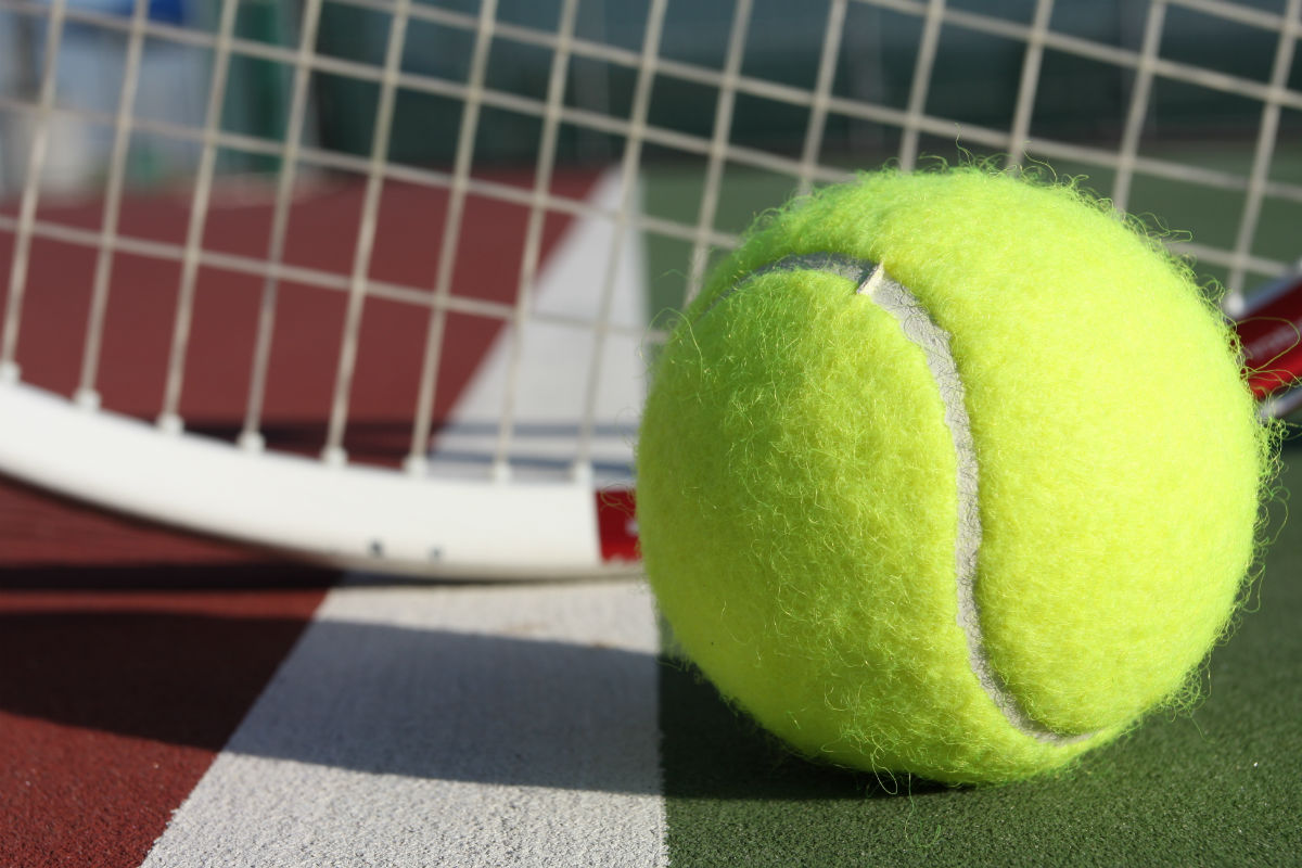Tennis ball with a racket behind it on a tennis court